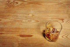 杯与冰的威士忌酒在老木桌上 免版税库存图片