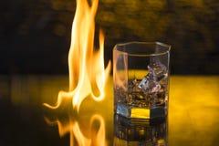 杯与冰的威士忌酒在黑背景和火发火焰 免版税库存图片