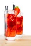 杯与冰的草莓鸡尾酒在轻的木桌上 免版税库存图片