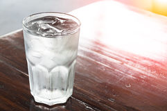 杯与冰的水在木桌,净水上 免版税库存照片