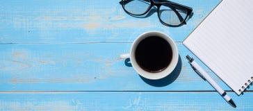 杯与办公用品的无奶咖啡;在蓝色木桌背景的笔、笔记本和眼睛玻璃 免版税库存照片