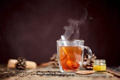 杯与匙子的热的金黄茶在木头桌上  免版税库存照片