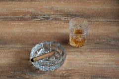 杯与古巴雪茄的威士忌酒在一张棕色木桌上 顶视图 免版税库存图片