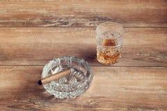 杯与古巴雪茄的威士忌酒在一张棕色木桌上 顶视图 库存图片