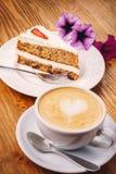 杯与可口蛋糕的新鲜的热奶咖啡咖啡在木桌上的胡萝卜蛋糕 免版税库存图片