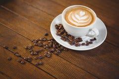 杯与咖啡艺术和咖啡豆的热奶咖啡 免版税库存图片