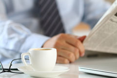 杯与商人的早晨咖啡在背景 库存图片
