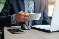 杯与商人的热的咖啡使用膝上型计算机和巧妙的电话,当工作在办公室时 库存照片