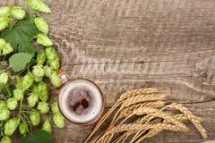 杯与啤酒花球果树和麦子的泡沫似的啤酒在老木背景 与拷贝空间的顶视图您的文本的 图库摄影