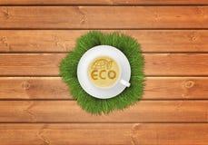 杯与图象ECO标志的热奶咖啡咖啡木表面上 库存照片