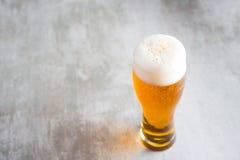 杯与在具体桌上的啤酒 免版税库存照片
