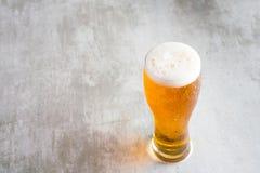杯与在具体桌上的啤酒 库存照片