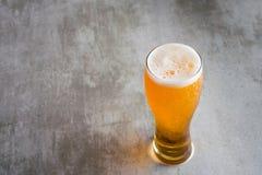 杯与在具体桌上的啤酒 免版税图库摄影