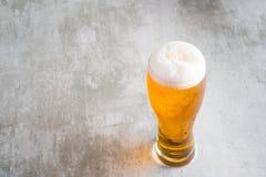 杯与在具体桌上的啤酒 免版税库存图片