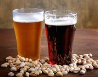 杯与坚果的黑暗和低度黄啤酒 库存图片