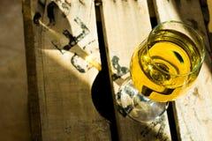 杯与富有的黄土铜焕发的白色马斯喀特酒在木箱子在阳光下 库存图片