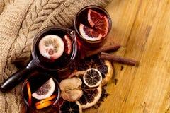 杯与干柑橘和香料,被编织的毛线衣的加香料的热葡萄酒 库存图片