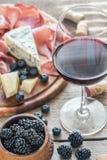 杯与开胃小菜的红葡萄酒在木桌上 图库摄影