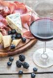 杯与开胃小菜的红葡萄酒在木桌上 免版税库存图片
