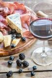 杯与开胃小菜的红葡萄酒在木桌上 库存图片