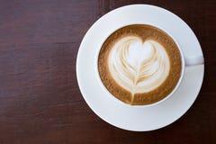 杯与心形的泡沫艺术的热的咖啡拿铁 库存照片