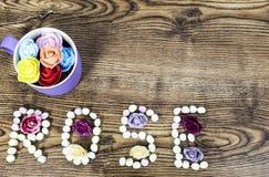 杯与文本玫瑰的按钮玫瑰形成了用在木桌上的蛋白软糖 免版税库存照片