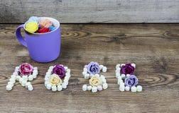 杯与文本玫瑰的按钮玫瑰形成了用蛋白软糖 免版税图库摄影