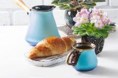 杯与新月形面包,土耳其咖啡罐,桃红色和白色非洲紫罗兰的无奶咖啡在白色桌上 免版税库存图片