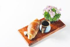 杯与新月形面包,桃红色和白色非洲紫罗兰的无奶咖啡在白色桌上 库存图片
