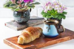 杯与新月形面包,桃红色和白色非洲紫罗兰的无奶咖啡在白色桌上 免版税库存图片