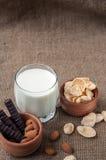 杯与杏仁坚果,玉米片,巧克力的牛奶,在袋装,粗麻布背景 库存照片