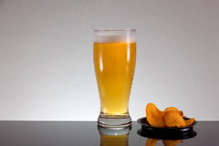 杯与泡沫的啤酒和在灰色背景的土豆片 库存图片
