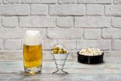 杯与泡沫的啤酒和碗用橄榄和玉米花 免版税库存照片