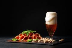 杯与泡沫,咸坚果,在黑背景的扭转的火腿的啤酒 刷新的酒精饮料 鲜美餐馆 库存图片