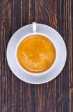 杯与浮渣的热的咖啡在木的茶碟在土气样式 库存照片