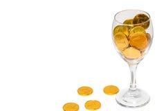 杯与溢出的金黄硬币的香槟 免版税库存图片
