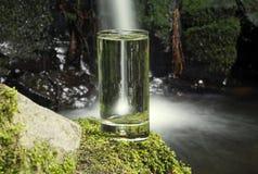 杯与瀑布的水在背景中 免版税图库摄影