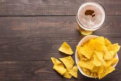 杯与烤干酪辣味玉米片的啤酒在木背景切削 免版税库存图片