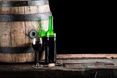 杯与瓶的酒和老橡木滚磨 免版税库存图片