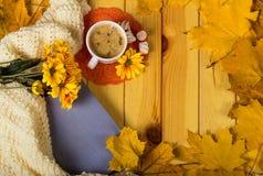 杯与甜点、秋天菊花和书的热奶咖啡咖啡在桌上 免版税库存图片