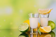 杯与石灰和柠檬的奶油色利口酒在绿色背景 图库摄影