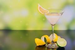 杯与石灰和柠檬的奶油色利口酒在绿色背景 库存图片