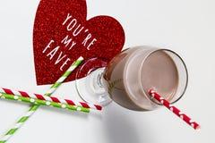 杯与红色和绿皮书秸杆和红色闪烁心脏的巧克力牛奶 库存照片