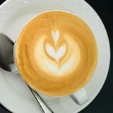 杯与艺术的热奶咖啡在白色茶碟,特写镜头 顶视图, 库存照片