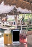 杯与苏打的草莓和芒果汁在一个木桌和智能手机上有黑屏幕的 热带的咖啡馆 库存照片