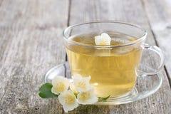 杯与茉莉花的绿茶在木桌上,水平 免版税图库摄影