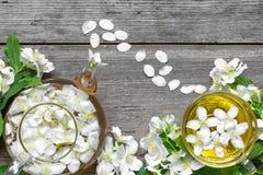 杯与茉莉花花和茶壶的绿色清凉茶在土气木背景 免版税库存图片