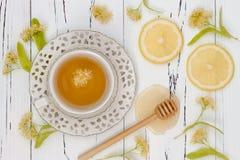 杯与菩提树花、柠檬和蜂蜜的清凉茶在老木背景 顶视图 库存照片