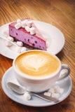 杯与蓝莓蛋糕可口片断的新鲜的热的咖啡在木桌上的 库存照片