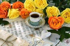 杯与装饰、音乐纸张和黄色玫瑰的红茶 免版税库存图片
